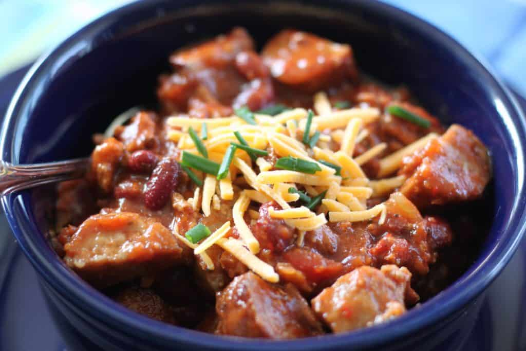 a chili recipe with sausage in a bowl after cooking it. The close-up photo is at an angle